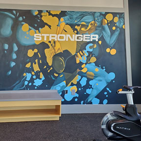 photo of gold and teal fitness center mural